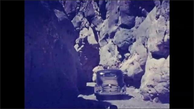 1920s: UNITED STATES: car drives through gap in mountains. Man walks along track. Man runs on path