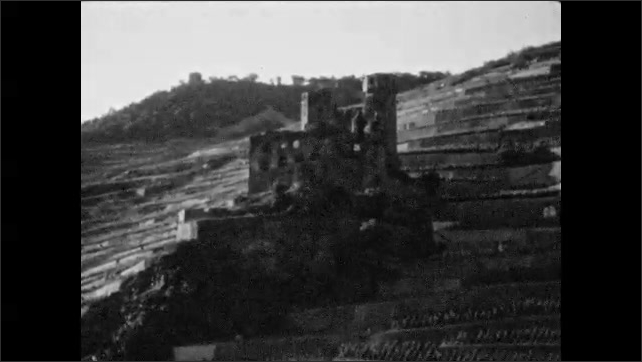 1920s: Tower peeks above mountain ridge. Steamboats and ships sail on large river. Ruined castle on tiered landscape. Woman in hat smiles and speaks.