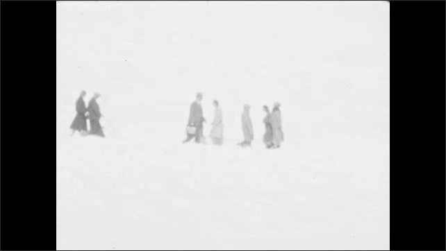 1920s: People trudge through deep snow on mountainside. People gather on snowy mountain road.