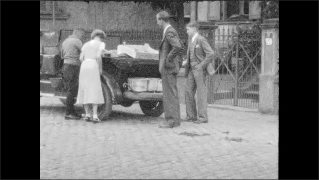 1930s: Men and women talk near iron gate. Men and women pose before stone wall. Men and women observe parked car. Men and woman pick items up off cobblestone street.