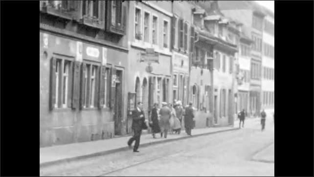1930s: Trees and homes along riverside. River winds through hills. People walk and bike through German city streets. German storefronts and signs.