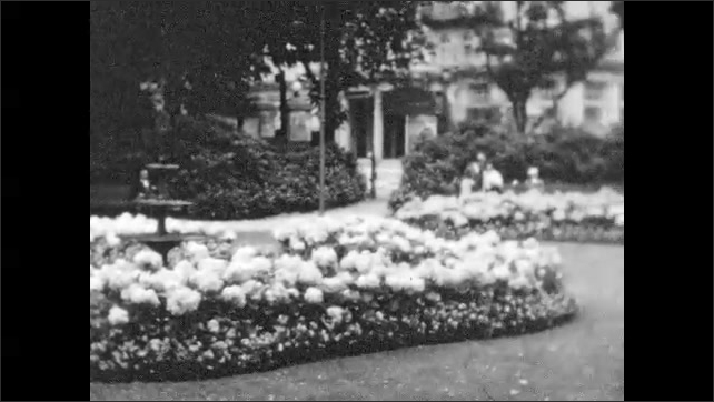 1930s: Men and woman walk up street. European village. People sit in flower garden near fountain. Title placard.