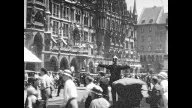 1930s: Crowds and traffic pour through streets of Munich. Police officer directs pedestrians and traffic. Bikes and cars speed along city streets.