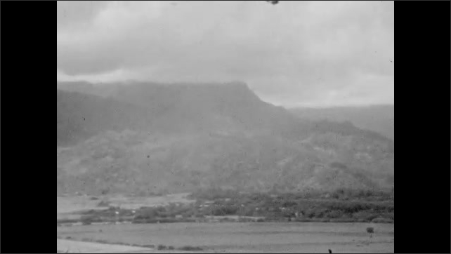 1920s: Water shoots from geyser near ocean. Waves crash on rocks near geyser. Men and women walk from ornate wood building. Mountain shoreline panorama.
