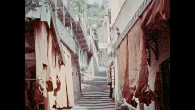1920s: men stand at iron railing and look at buildings on Lake Como. white steps go up near closely built houses with balconies and curtains. water fountain near staircases to home. trees near pond.