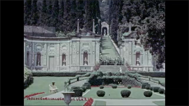 1920s: buildings and homes rise on green hills around Lake Como as boats sail. Italy. woman in white dress walks up long staircase in the lush and elaborate gardens of Villa d'Este, Cernobbio.