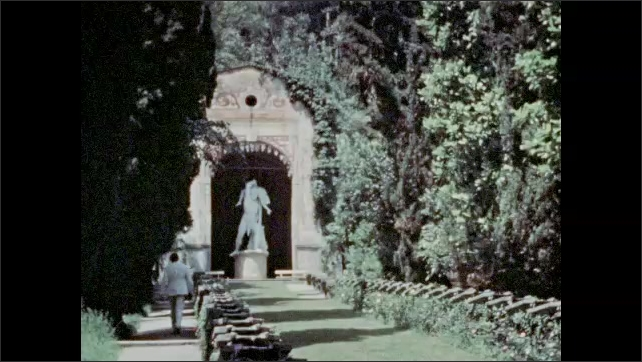 1920s: woman in white dress waves and walks up hill path to a statue of man in loincloth holding a person in  Villa d'Este, Cernobbio on Lake Como, Italy. man stands by art as girl sits on bench.