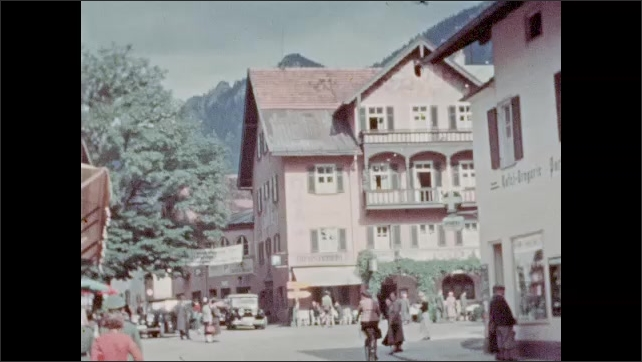 1920s: men and woman walk down street near decorated house with ivy on wall in Alpine village. guys in lederhosen stand by convertible touring car. diners eat outside hotel and restaurant.