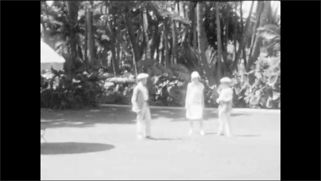 1920s: A family walking down a path and on a lawn among palm trees.