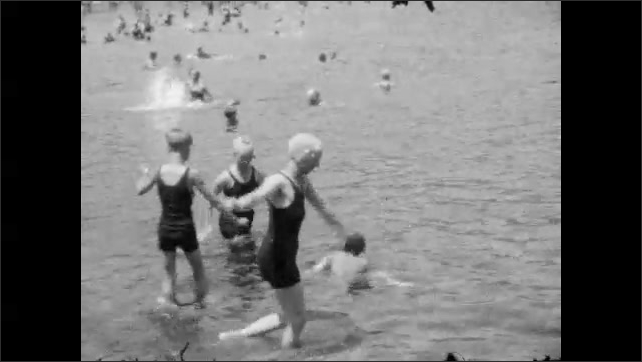 1920s:  UNITED STATES: lady takes off trousers on beach. Lady walks into sea. Lady underwater