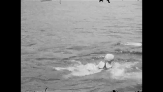 1920s:  UNITED STATES: boy swims in sea. Boy splashes in water. Lady swims in sea. Family relax at beach