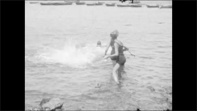1920s:  UNITED STATES: family play in sea. Man looks at camera. Family walks into sea. Boy looks at camera. Man swims in sea.