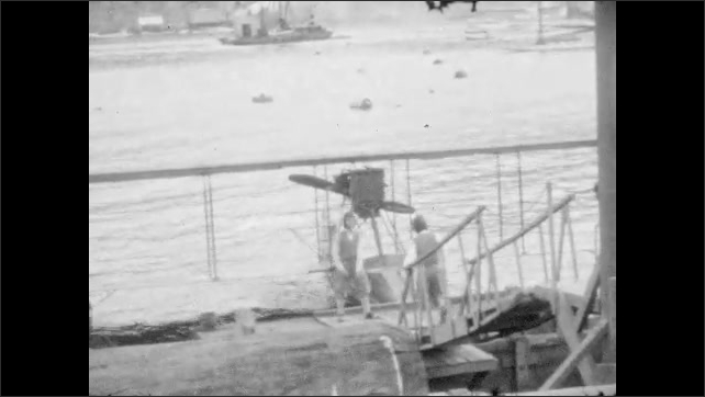 1920s:  UNITED STATES: men put on flying hats. Boys run towards boat. Boys in pilot costumes. Man helps boys into boat