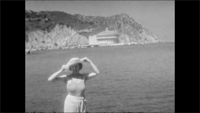 1920s:  UNITED STATES: boy walks into sea. Boy splashes camera. Lady takes off hat. Lady changes into swimwear on beach