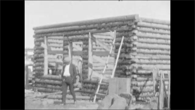1920s: Cabins and low buildings on shore. Well-dressed woman and two sons walk through log cabin under construction. Woman and two sons walk down dirt road.
