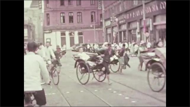 1930s: Men push and pull heavy loads.  Men run down the street with rickshaws.