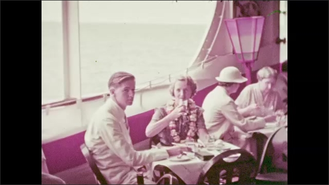 1930s: Island.  People eat on deck of cruise ship.  Man stands.  Buffet.
