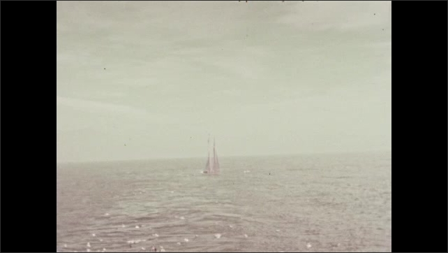 1930s: Sailboat.  Men leave cruise ship in row boat.  Birds fly over ocean.  Passengers stand on deck.