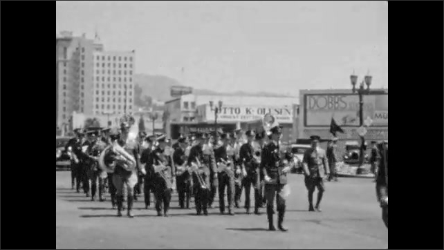 1940s: Soldiers carry rifles, flags and instruments and march down city street. Women in uniform carry flags and march in streets.