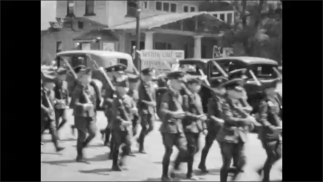 1940s: Soldiers and cadets carry flags and rifles in parade.