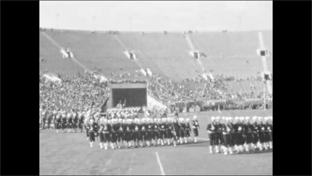 1940s: Soldiers carry rifles and march into crowded stadium. Military marching band walks onto field in crowded stadium.