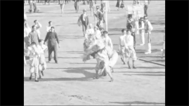 1940s: Marching bands parade in field. Costumed man rides horse. Men in Native American garb walk onto field. Men perform with Chinese Dragon costume. Horses pull large float of Cathedral.