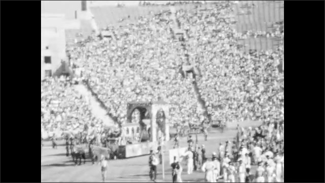 1940s: Horses pull floats of elaborate buildings through crowded stadium.