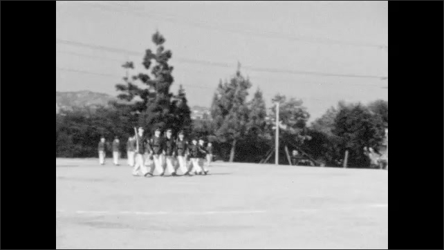 1940s: Military cadets march in formations in field. Military cadets salute superiors and stand at attention.