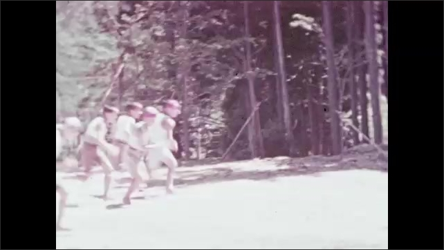 1930s: Children marching in formation. Girls run in competition. Boys run in competition then climb poles, touch the top then slide down. Girls run to poles.