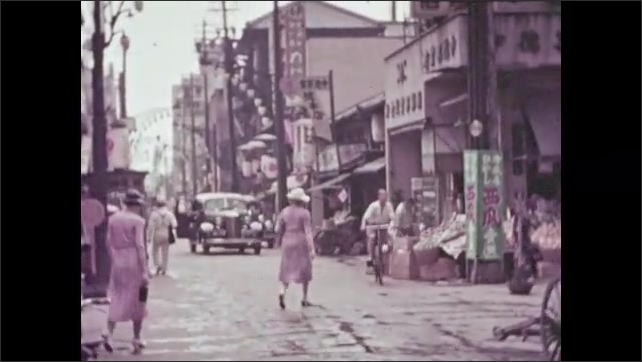1930s: People walking and riding bikes down village road, passed street vendors, in Japan. Truck with load waits on street.