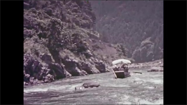 1930s: Boat going down river. People in boat, waving. Boats going down river. Busy village road.