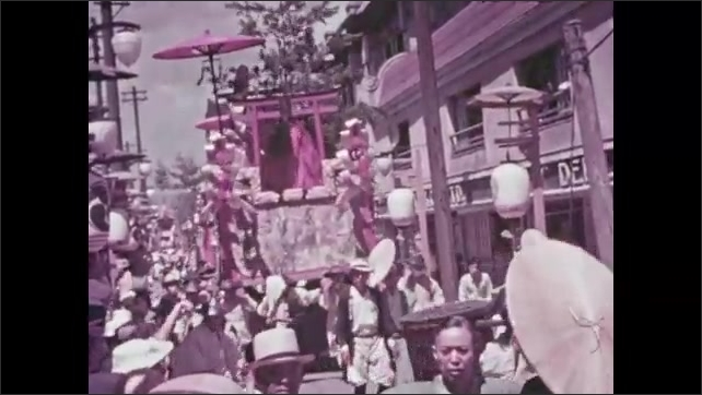 1930s: Men carrying float in parade down street in Kyoto. Floats go down street in parade. Men carrying float. Men resting with float.