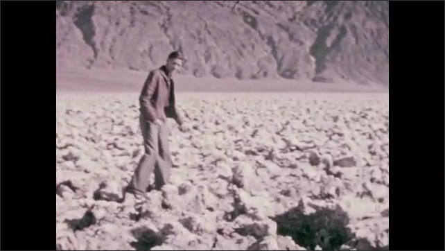 1920s: Man walks across stones in pool, balances, dips hand into water. Man walks around ground made up of craggily, sharp rocks.  Sharp rocks. Car parked in distance, mountains on horizon.