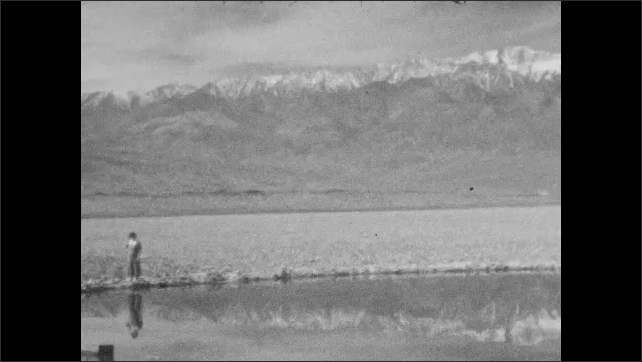 "1920s: Woman stands at pond in middle of desert, mountains on horizon. Sign ""SALT POOLS ????I AUTOMOBILE CLUB SOUTHERN CALIF"".  Man and women walk among rocks, mountains on horizon."