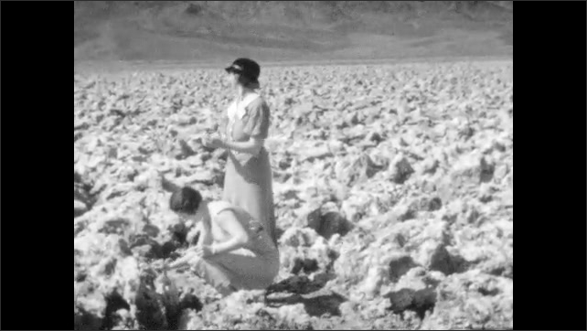 1920s: Man and women walk throw field of rocks. Women crouch and inspect rocks. Women smack rocks together. Man in hat and glasses sticks hand into pool of water, flicks water off of finger.