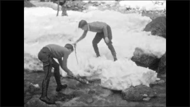 1930s: Two boys poke at snow around river bank. Waterfall. Car at base of waterfall.