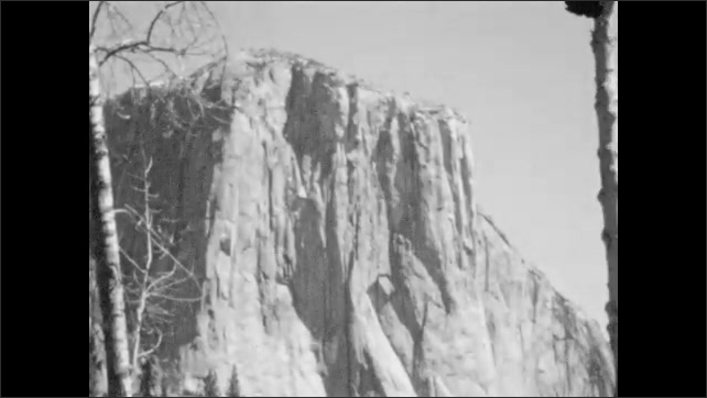 1930s: Waterfall. El Capitan rock formation in Yosemite. People throw rocks near river at base of El Capitan.