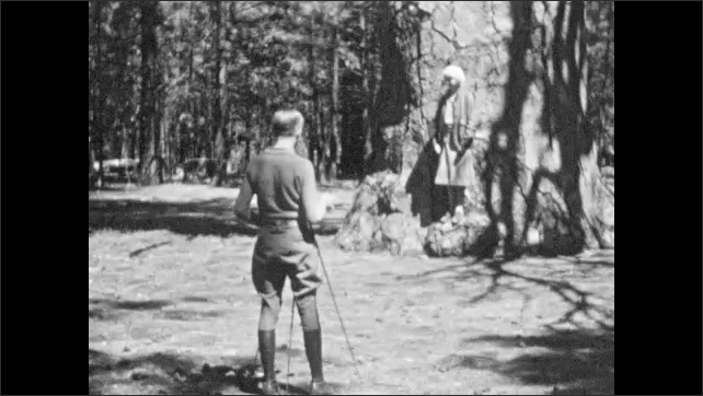 1930s: People stand by river, woman throws rock. Sign for Giant Yellow Pine. People stand in front of tree, holds out arms, man adjusts camera on tripod.