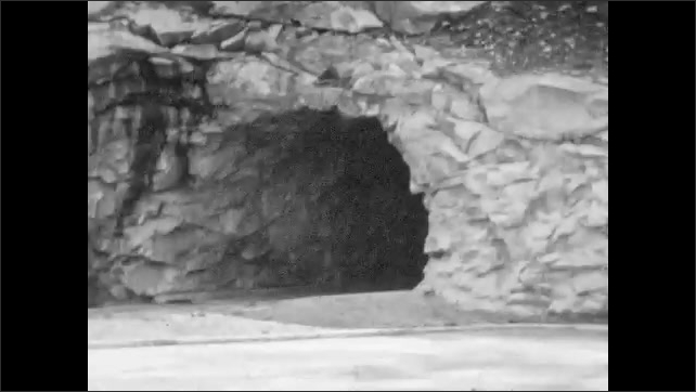1930s: Cars drive into mountain tunnel. Car drives out of mountain tunnel.