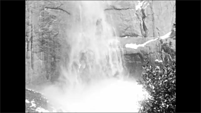 1930s: UNITED STATES: waterfall in rock face. Water falls down cliff. Pool at bottom of waterfall. People by waterfall