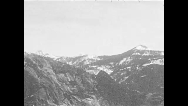 1930s: UNITED STATES: snow and scree on mountain side. View towards mountain peaks. Boys walk up mountain path