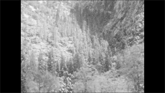 1930s: UNITED STATES: children walk along path in forest. Trees on mountain slopes. Sky above mountains. House in valley