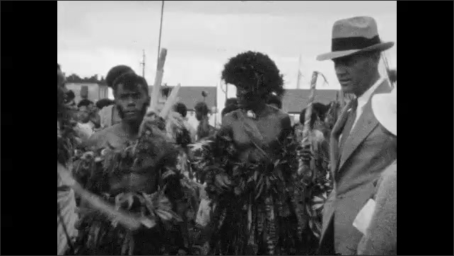 1930s: Men in native dress pose in formation.  Shots of people in native dress. Long shot, woman standing in front of structure.