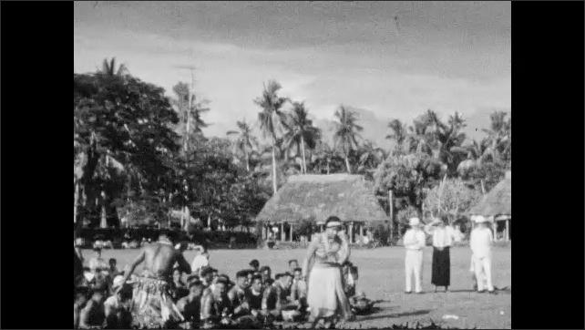 1930s: Woman and men dancing in front of seated dancers, woman walks toward camera. View of men dancing.