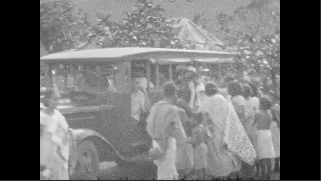 1930s: People in native dress, woman holding fabric. Woman on ground with baskets, woman enters frame. People standing outside. People gathering around car. Woman unfolds cloth.