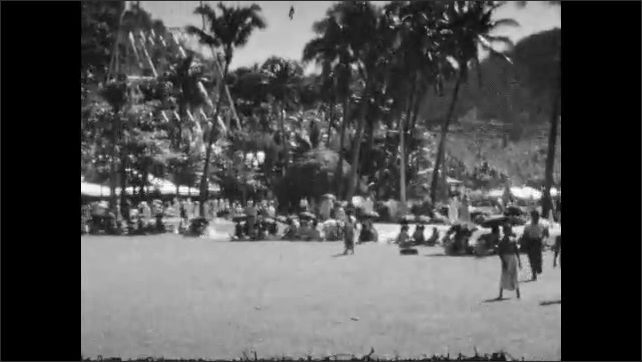 1930s: People sitting on grass. Kids playing on grass. Long shot of kids playing, people on grass. Woman in native dress dancing, people on ground clapping.