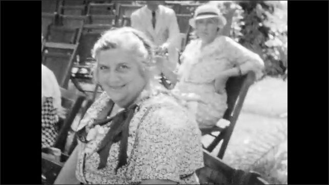 1930s: Man chopping coconuts. Crowd watches man chop coconuts. Close up, man chopping. Pan across people in chairs. Woman dances and sings in front of band.