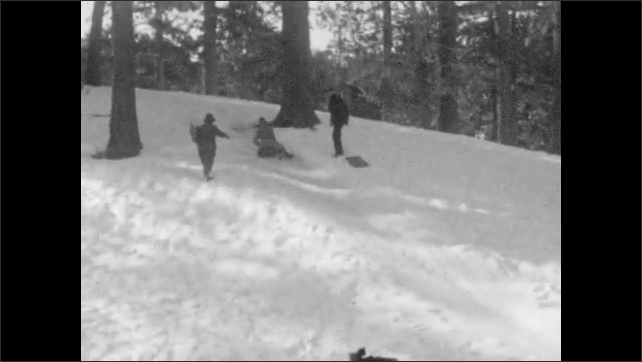 1930s: Person tries to sled down snowy hillside, scoots sled, stands up, picks up sled. Person sleds down hill quickly, gets stuck, stops, adjusts sled.
