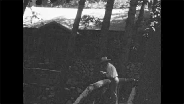 1930s: Man in hat fishes from wooden bridge outside lodge. Man stands on bridge and tips hat.