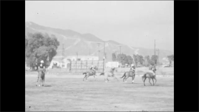 1930s: Men on horseback play polo in field. Teams of polo players chase ball up and down field.